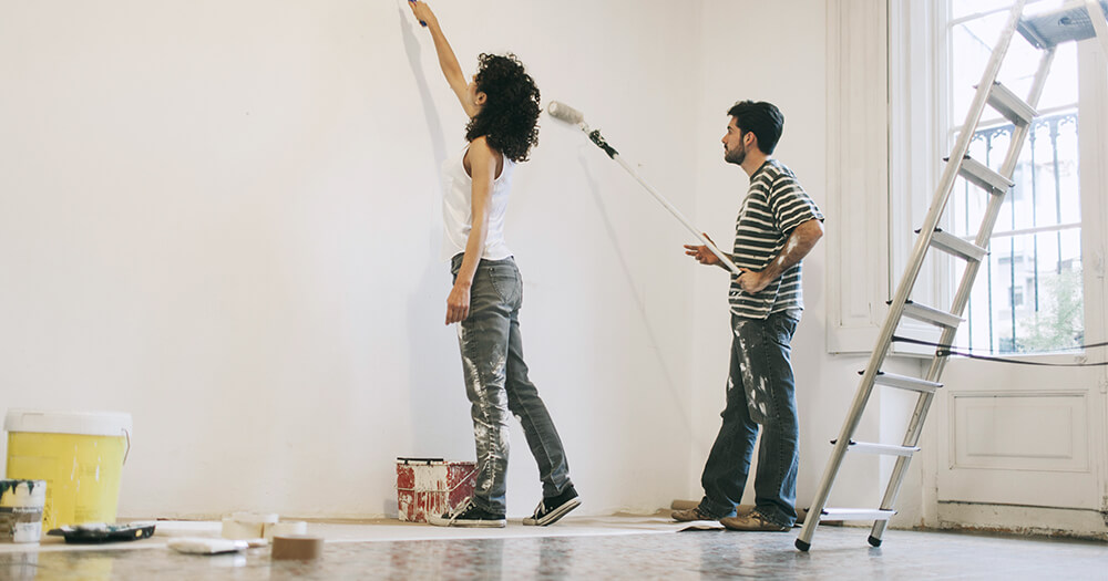 Couple painting the walls white