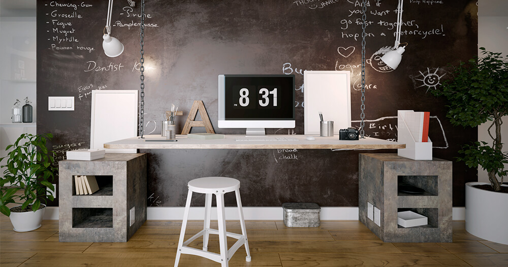 Rustic industrial home office with blackboard, white stool, concrete bricks, plants and lamps, and wooden floors
