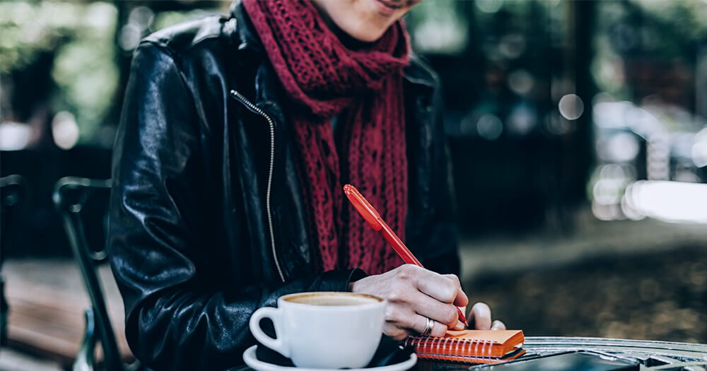 Lady in leather jacket and red scarf, writing in journal, outdoors