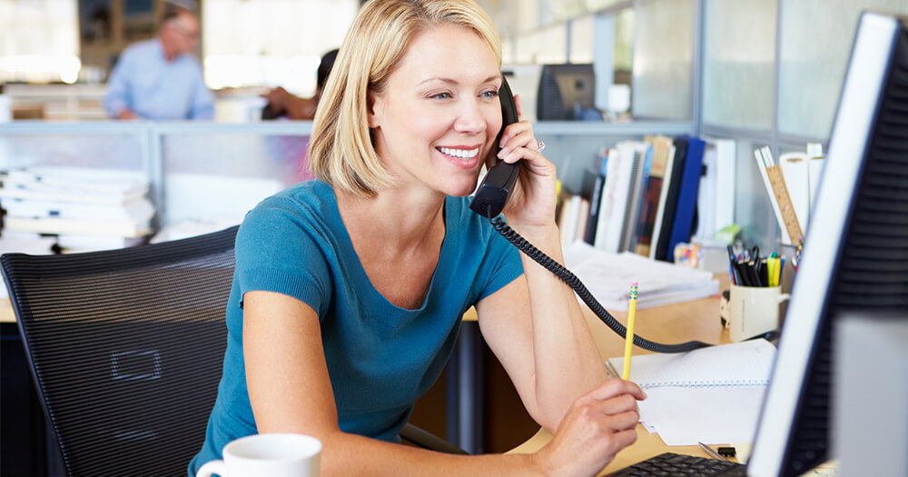 Blonde lady sitting at office desk on telephone is growing your career