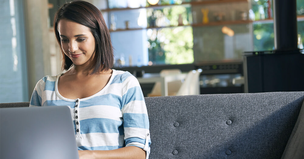 Young adult woman in stripe blue shirt working from home hapilly on the couch
