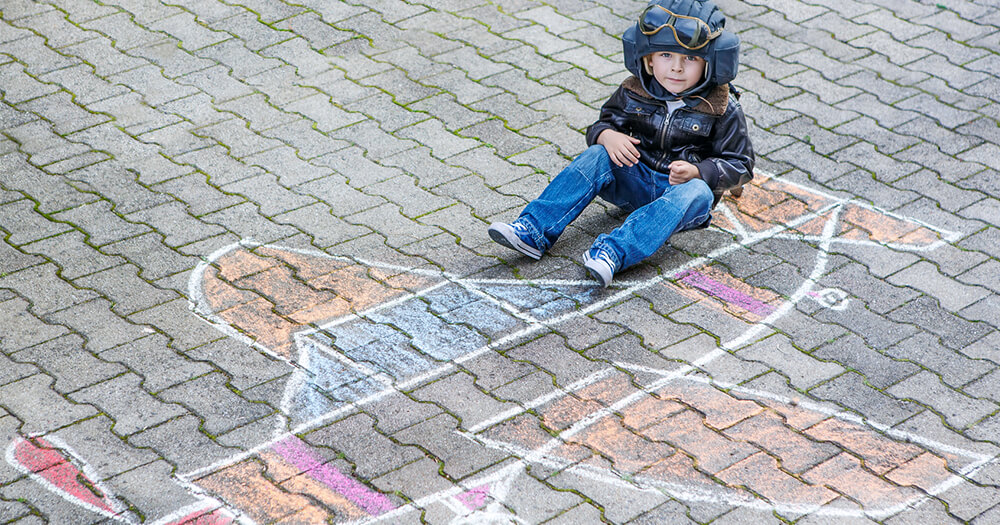 Young little boy business entrepreneur sitting on a pavement chalk drawing of an aeroplane and wearing a pilot's helmet