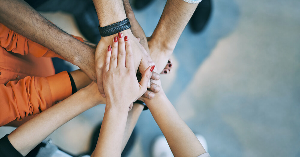 Group of diverse hands on top of each other to show team support for how to succeed in business