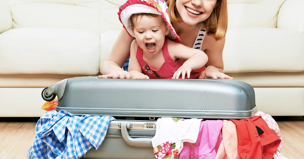 Mother packing a stuffed suitcase and holding a baby girl