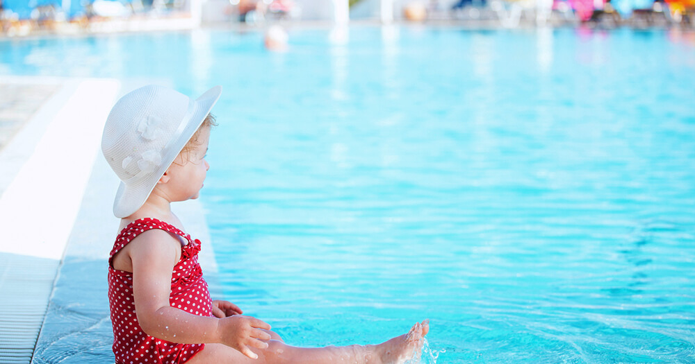 Family friendly hotel pool with baby in red polka dot swimming costume and white hat