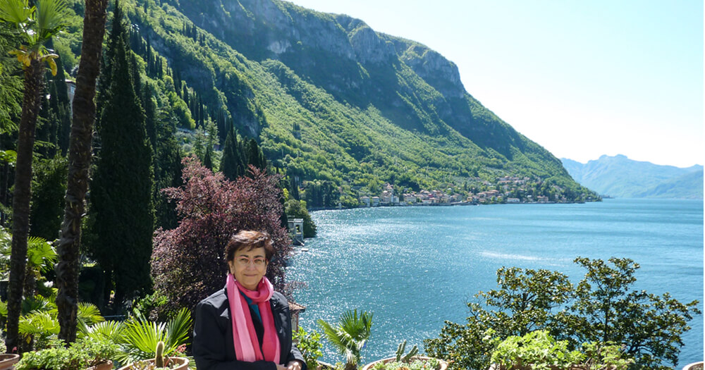 Lake como with photography student surrounded by sea mountains and buildings