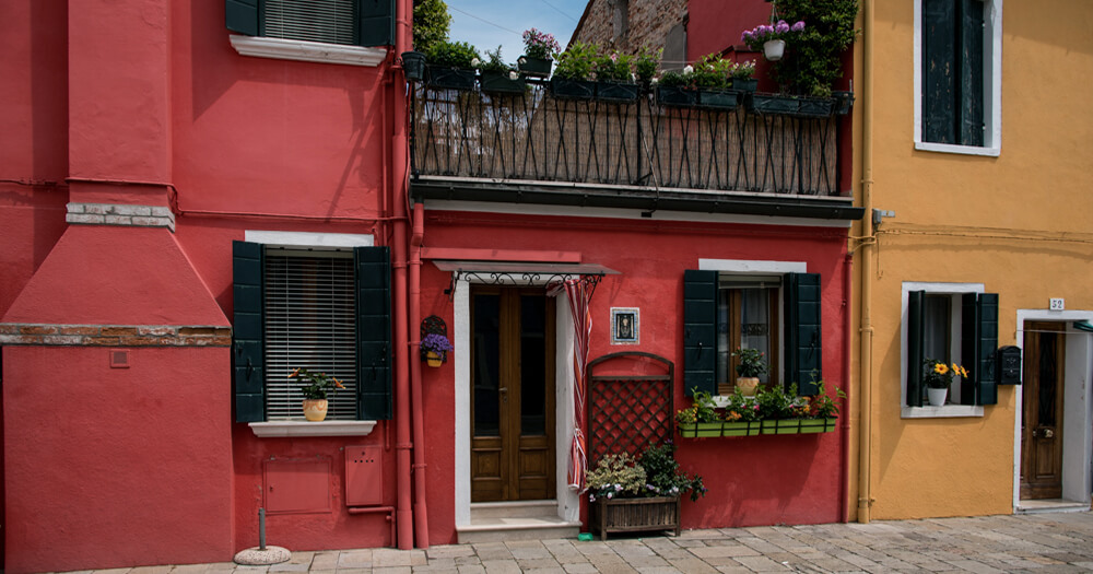 Beautiful colourful buildings in Europe, red and yellow, with plants, lattice and wooden door