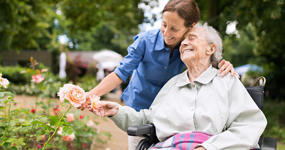 Happy individual support and aged care worker and smiling elderly lady smelling the roses outdoors in garden