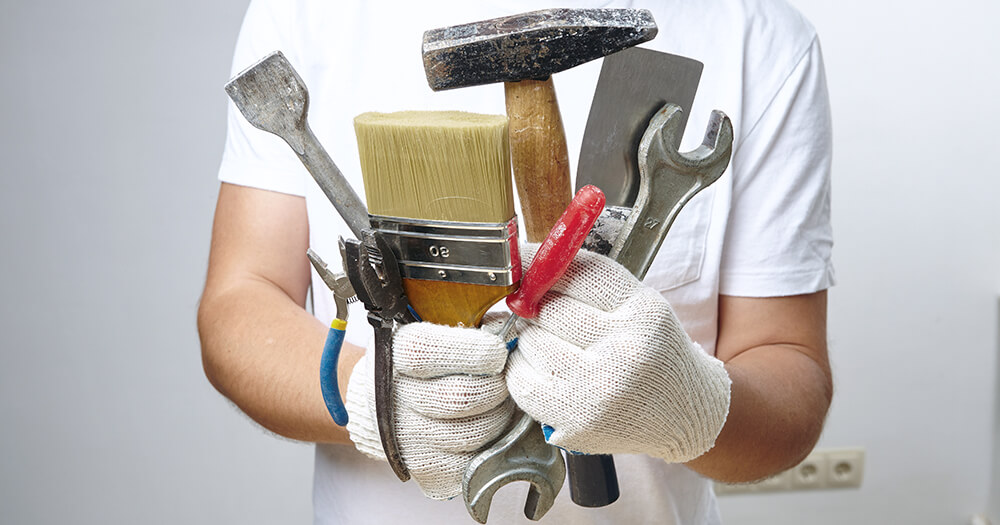 Man who is the jack of all trades in a white t-shirt holding many tools in his gloved hands