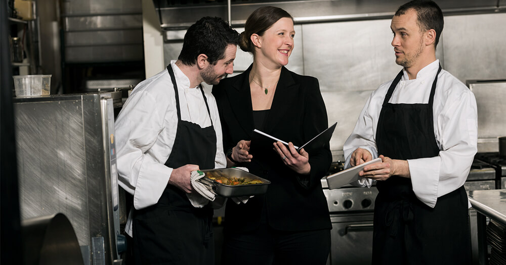 Food and beverage manager working with chefs in a kitchen
