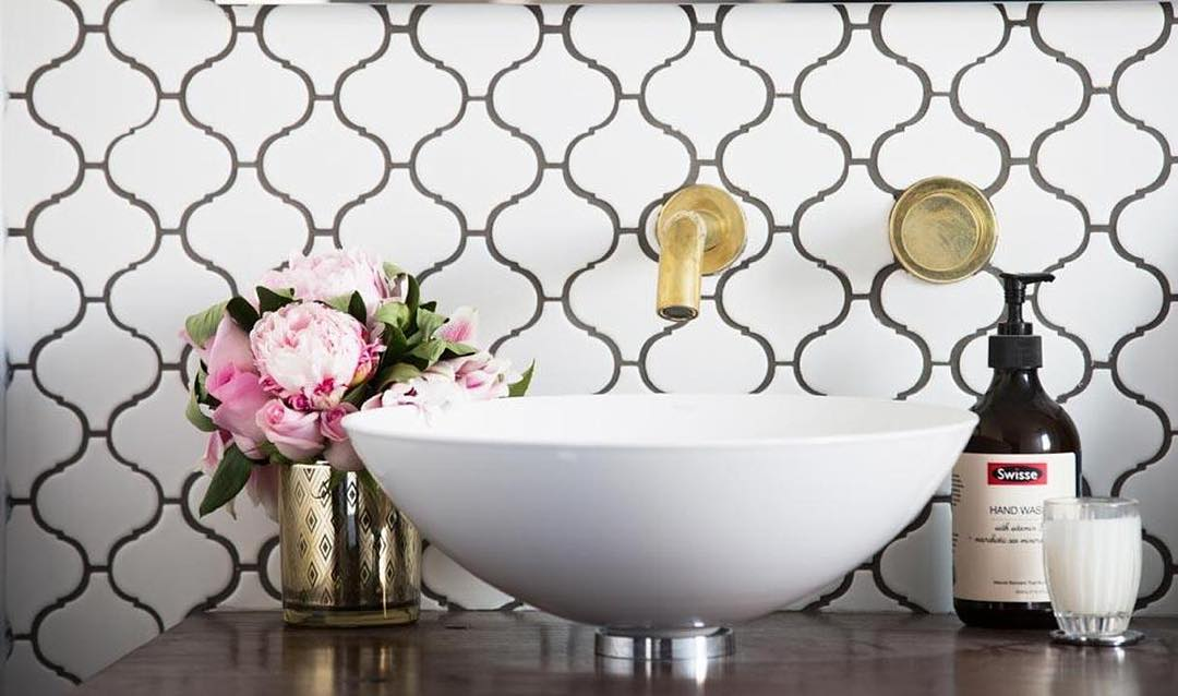 Beautiful white mosaic tiles with gold tapware and pink flowers