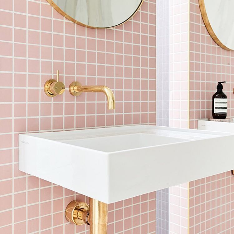 Blush pink coloured tiles with gold tapware