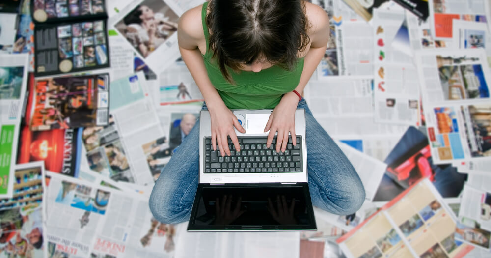 Brunette girl using her laptop and searching for information, sitting on a pile of print magazines and advertisements