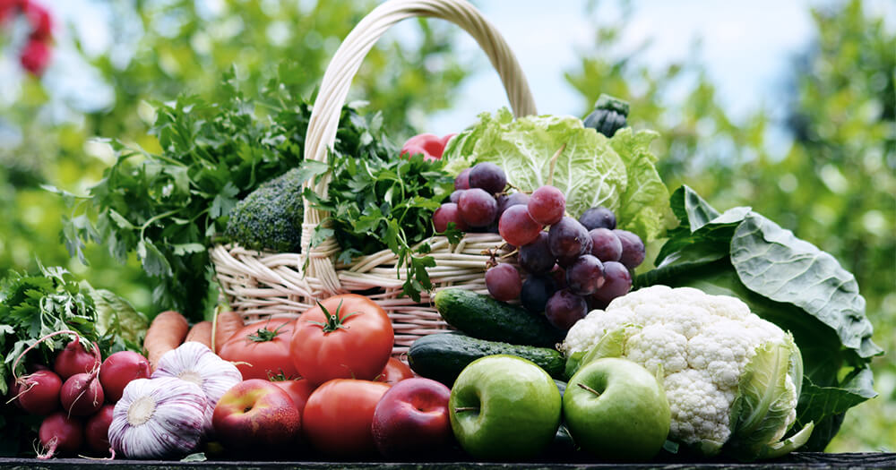 Detox cleansing with healthy whole foods vegetables and fruits in a basket in the garden