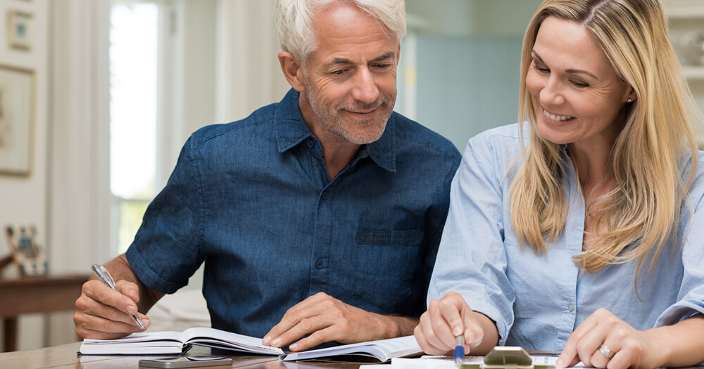 Mature couple working out home personal finances to get the best value for money