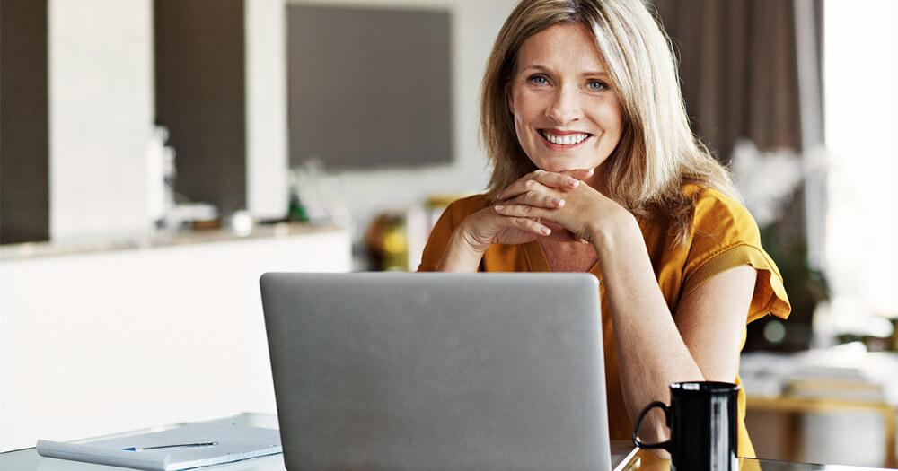 Mature woman student reading money tips at home on laptop with coffee