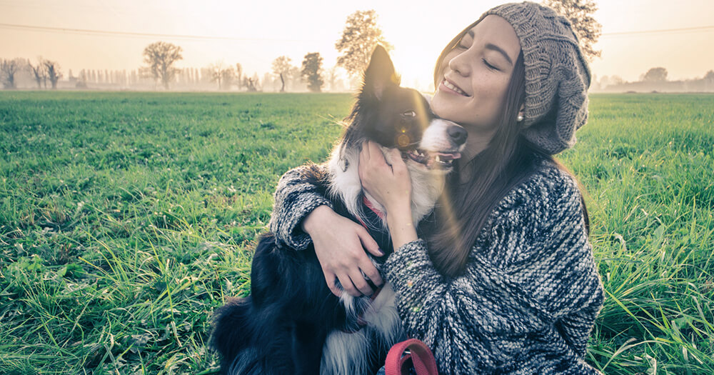 A young grateful girl in beanie and a border collie dog hugging out in a field of grass