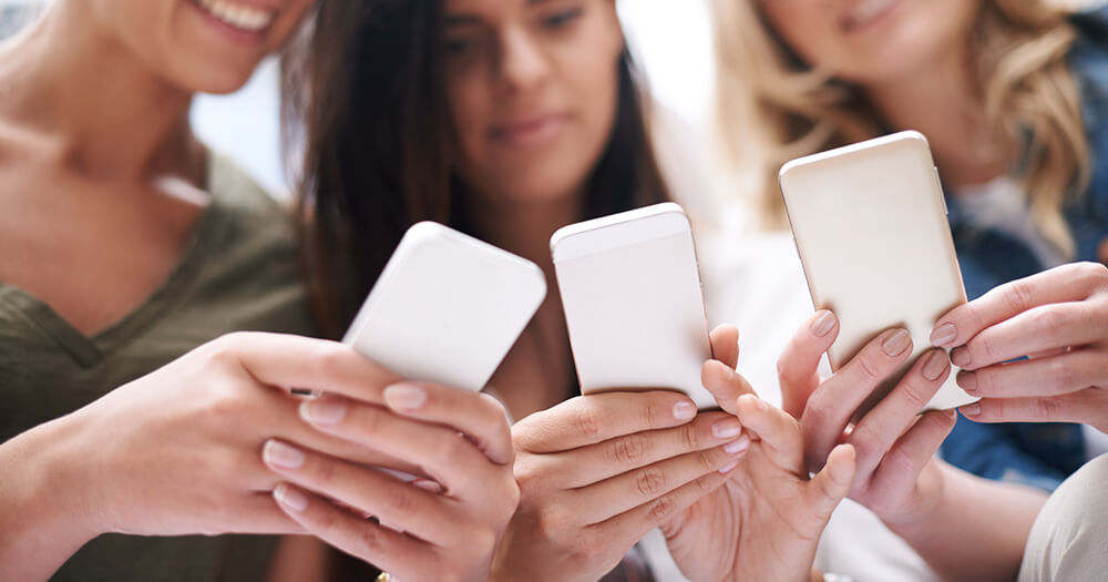 Group of girls using smartphone for social networking