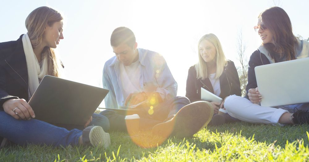 Social media marketing students sitting on grass and chatting