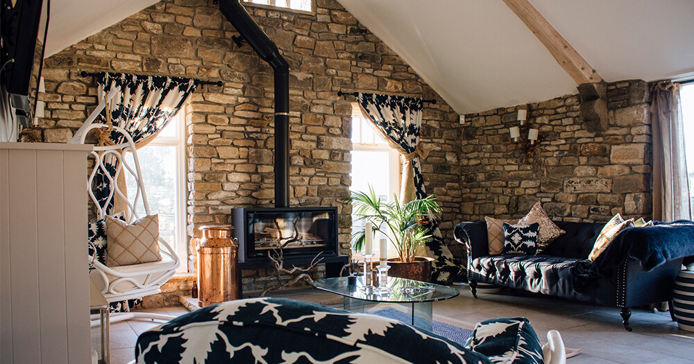 Interior design inspiration: Cosy stone corner with fireplace, blue upholstery, curtains
