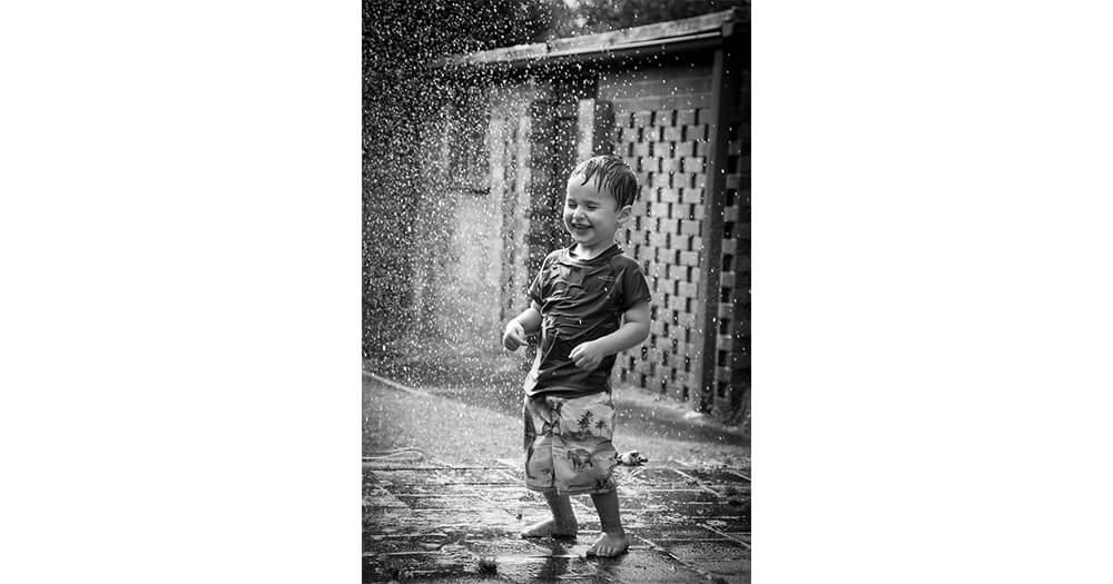 Black and white photo of child in rain, Nicole's first photography job
