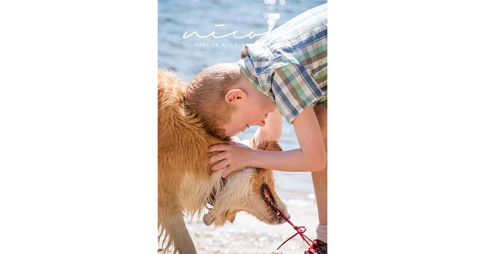 Boy and dog playing at beach - Nicole King photography