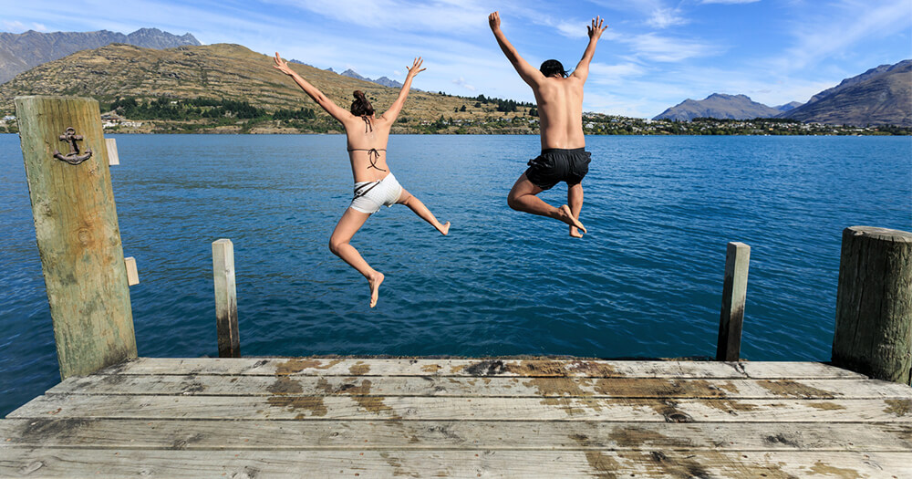 One and one female jumping off wharf into the sea with a mountain landscape in the foreground to stop fearing failure