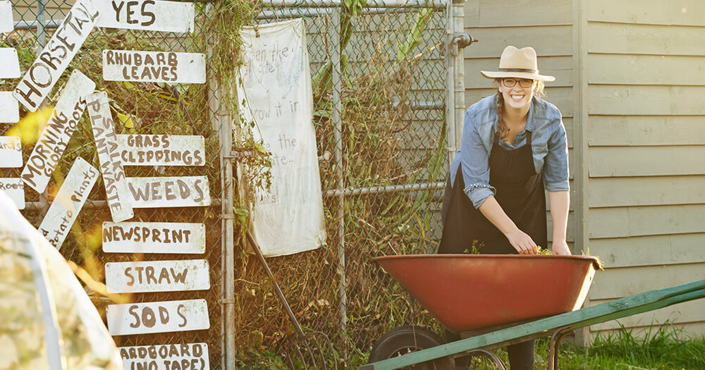 A lady in a hat with a wheelbarrow advocates sustainability in hospitality by recycling and composting