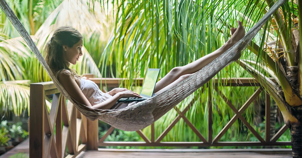 Digital nomad girl lying in a hammock in the tropics and working