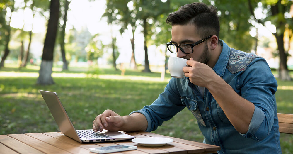 Young man studying and working outdoors