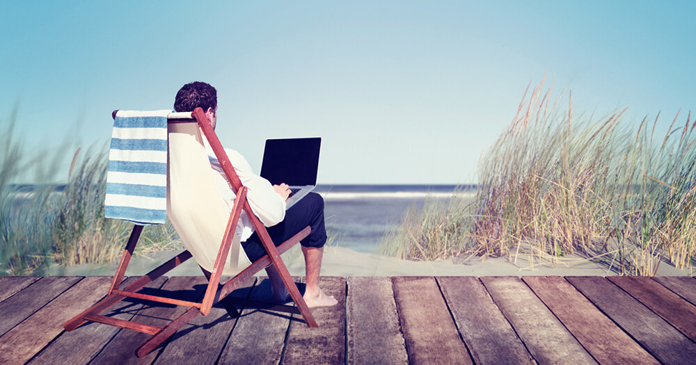 Man with sandy feet working remotely facing the beach on a deck chair