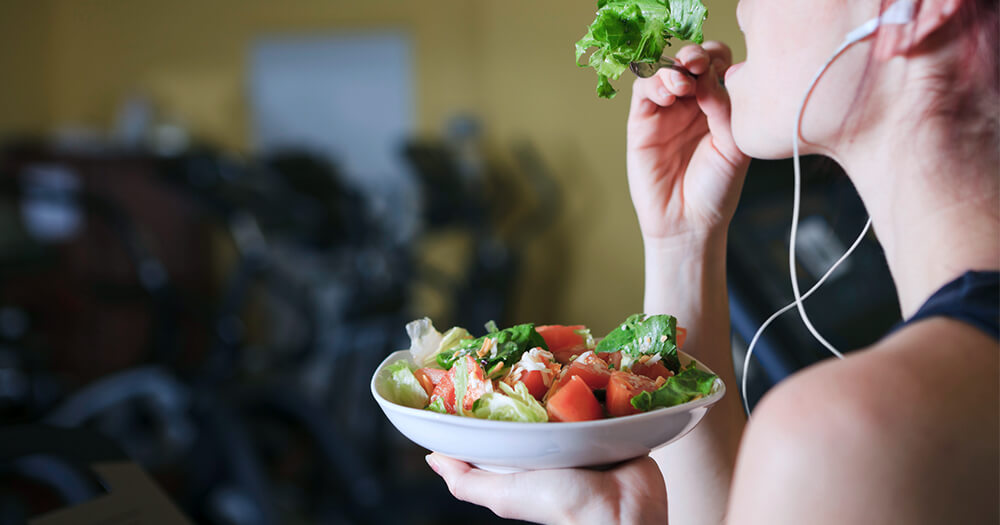 Girl at the gym eating a salad