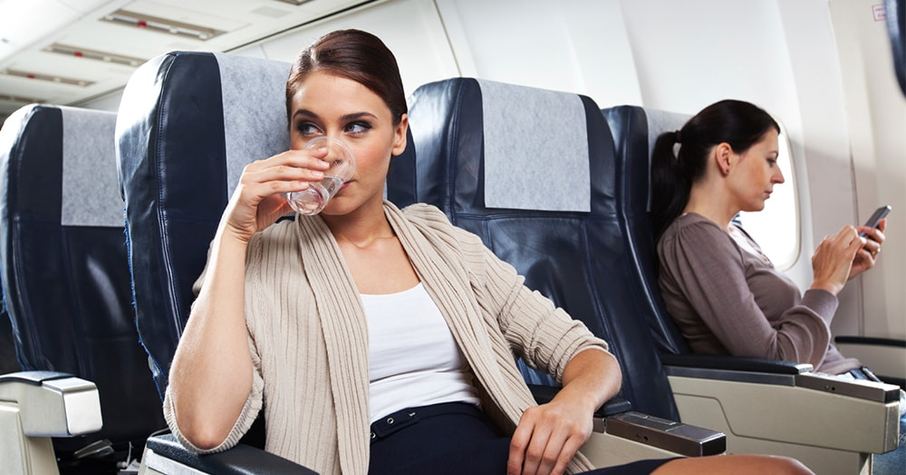 Travel tips - drink water - woman on plane to new city