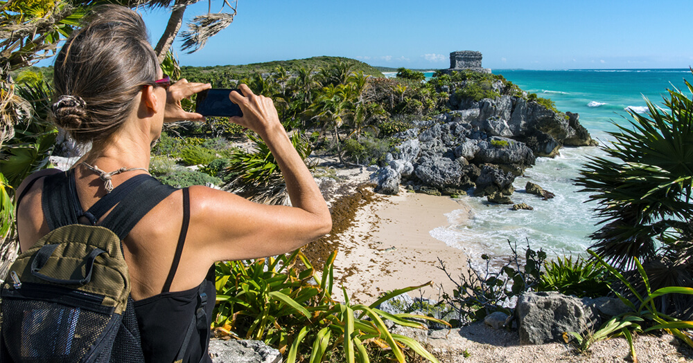 Lady taking a photo of Tulum on smartphone - engage with your social media audience
