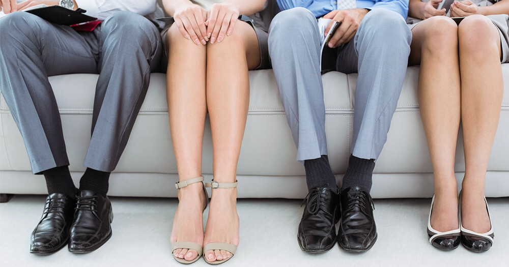 Four sets of legs, 2 male and 2 female, waiting in a job interview room, wearing professional attire