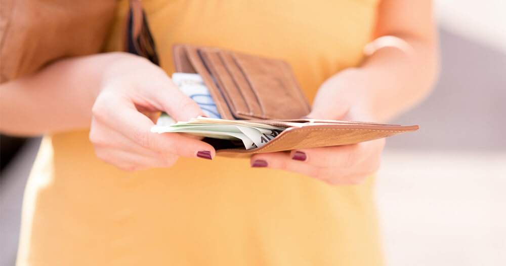 Woman working for yourself checking money contents of wallet