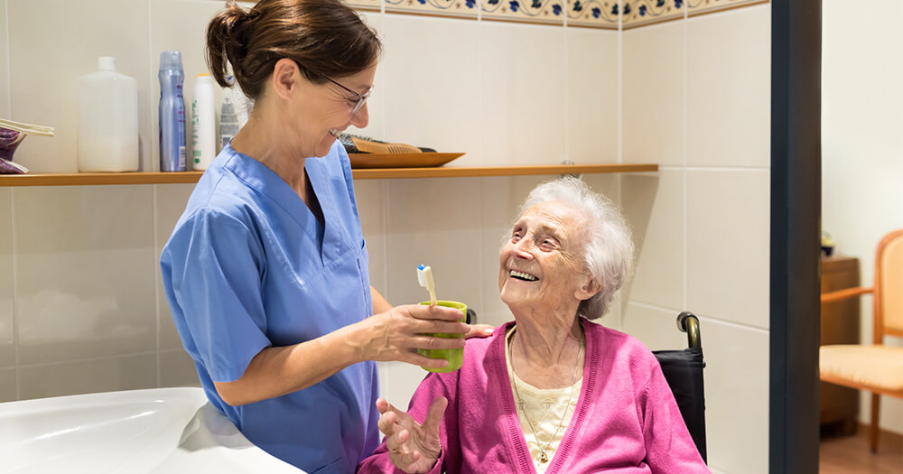 Aged care worker working in aged care with elderly lady in bathroom