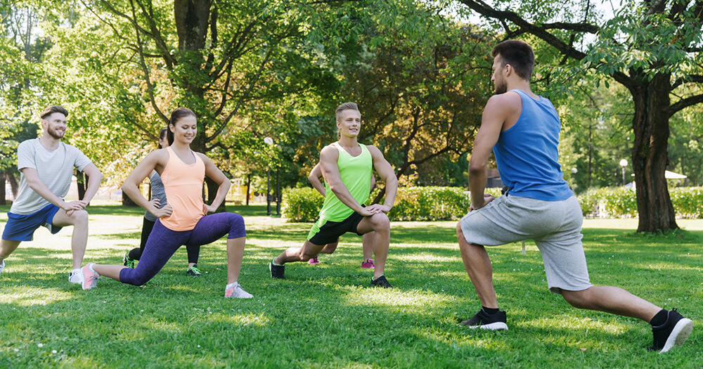 Personal trainer with his fitness class in the park