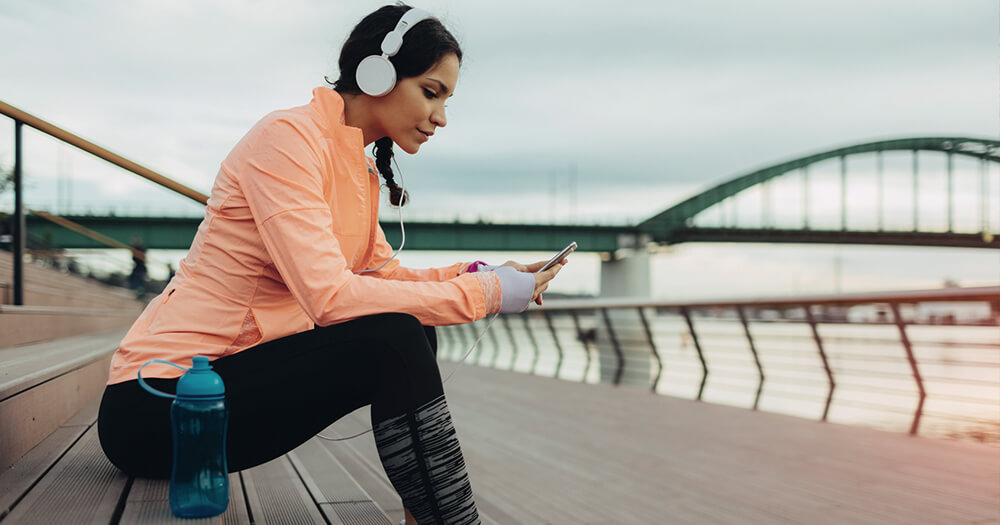 Fit girl in orange top and headphones resting and checking her phone