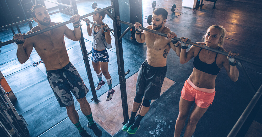 Fitness trainer who is training his clients in the gym on the chin up bar