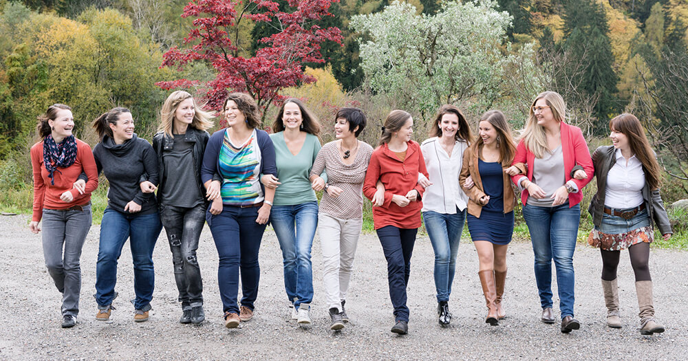 Group of casually-clothed female friends standing in a line outdoors in front of trees, smiling and supportive