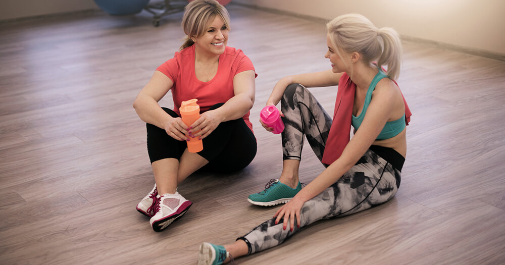 Female fitness trainer sitting down in the gym and asking her client for a referral