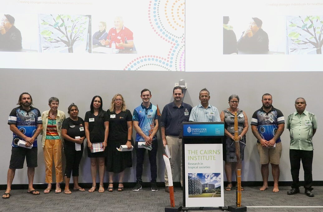 Les Baird (behind lectern) standing with presenters from Family Wellbeing sites around Australia