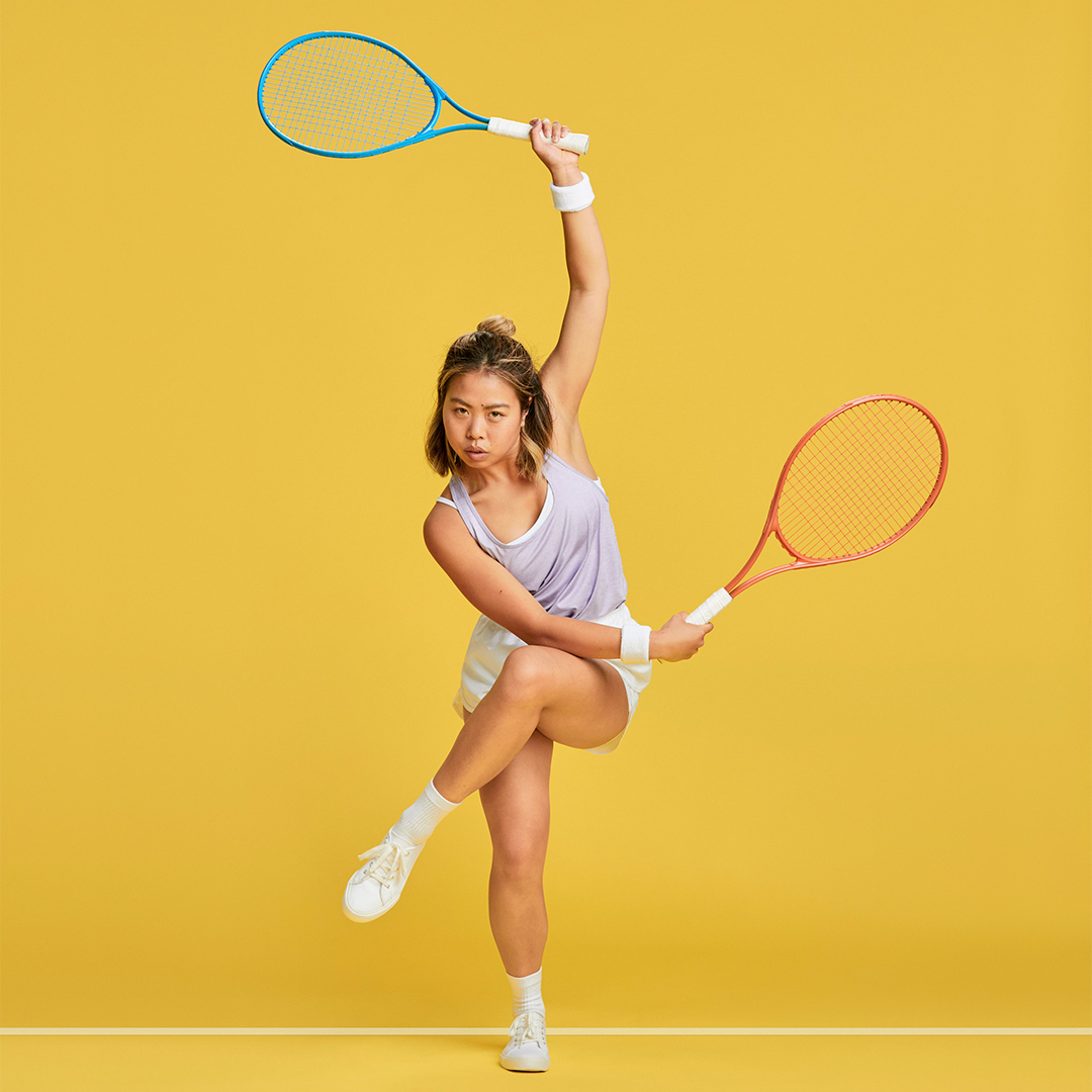 Two hand racquet jumping over fence yellow