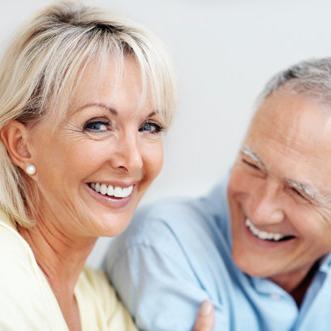 Senior couple smiling undergo dental crown treatment