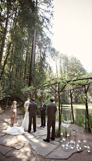 An arch made of branches and surrounded by candles green wedding shoes