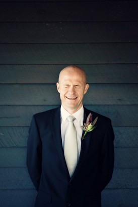 Groom in navy suit with pearl tie