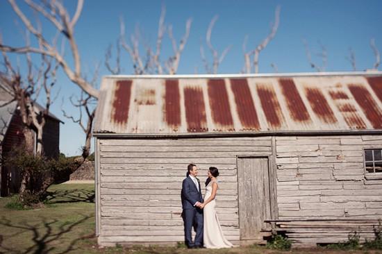 bride and groom against barn
