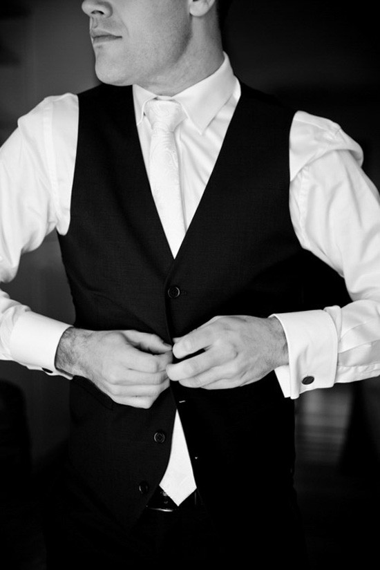 groom putting on black waistcoat