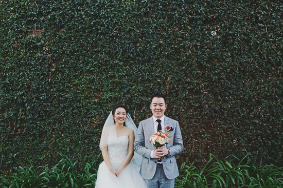 Bride and groom in front of ivy wall